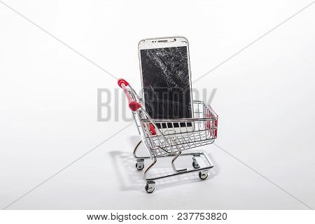 Broken White Phone Display In Shopping Cart. Scattered And Broken Display On A Mobile Phone. For Rep