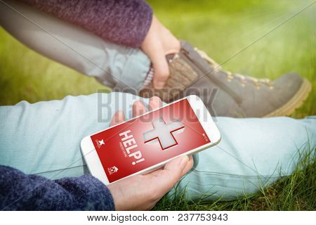 Injured woman holding her painful leg and calling rescue team with simple user-friendly smart phone application