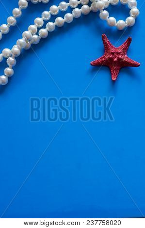 Artificial Pearls And Starfish On A Blue Background