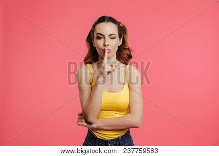 Mystery brunette woman in casual clothes showing silence gesture while winks with eye and looking at the camera over pink background