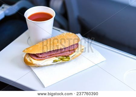 Economy Class Inflight Meal, Sandwich And Tomato Juice On The Folding Table.