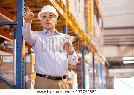 Professional Logistics. Serious Skilled Manager Pointing With His Hand While Controlling The Working