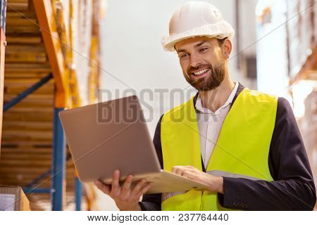 Modern Device. Positive Delivery Manager Using A Laptop While Controlling The Working Process