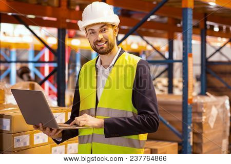 Portable Gadget. Delighted Logistics Manager Holding A Laptop While Working With A Logistic System O