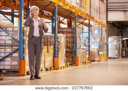 Storehouse Manager. Professional Female Manager Talking On The Phone While Discussing The Working Is