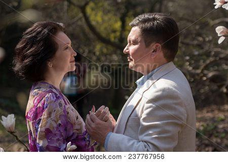 Elegant Age Pair In The Garden Of Magnolias. Wedding Walk. True Love. Adult Couple Walks In The Blos