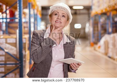 Working Issues. Pleasant Nice Woman Thinking About The Problem Solution While Working As A Storehous