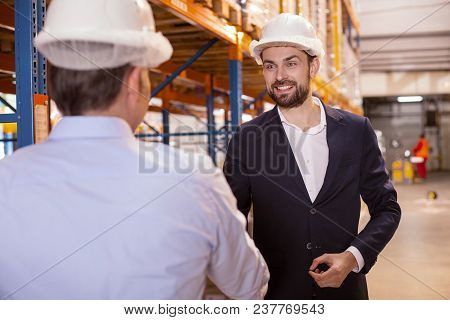 Friendly Greetings. Joyful Smart Businessman Looking At His Warehouse Manager While Greeting Him