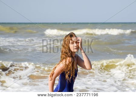 A Blonde Girl In A Blue Bathing Suit On The Beach. Beach Holidays