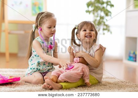 Two Children Kids Friends Playing Doctor With A Doll In Kindergarten