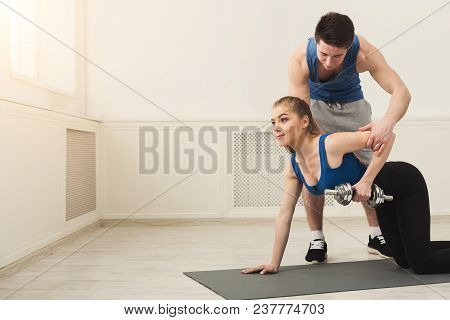 Fitness Woman Training With Her Personal Trainer At Gym. Young Couple Doing Strength Exercise For Bi