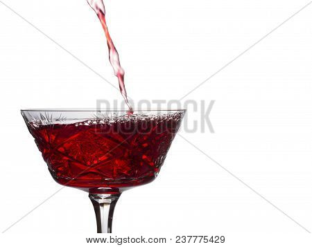 Bright Stream Of Red Wine Pours Into A Vintage Glass Of A Delicious Drink From Grapes