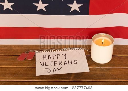 American Flag And Army Tokens On Veterans Day . Memorial Candle . On Wooden Background