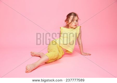 Little Charming Girl In Yellow Outfit Doing Splits While Sitting On Pink Backdrop Looking Expressive