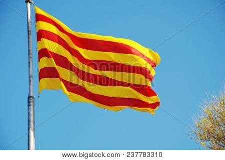 La Senyera, the red and yellow flag of Catalonia flying in Barcelona, Spain.