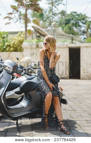 Attractive Blonde Woman Sitting On Motorbike In City In Summer
