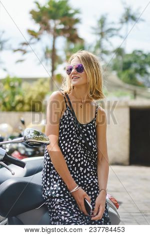 Blonde Woman In Sunglasses Leaning On Motorbike In City