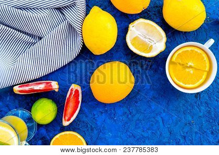 Hot Fragrant Tea With Fruits. Teacup And Teapot Near Citruses On Blue Background Top View.