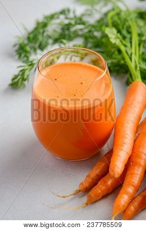 Fresh Carrot Juice On A Gray Concrete Background, Selective Focus.