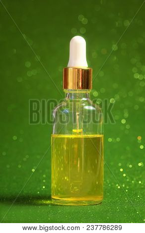 Vivid Golden Beauty Cosmetic Oil Stands In Clear Dropper Bottle On Shiny Green Holiday Background