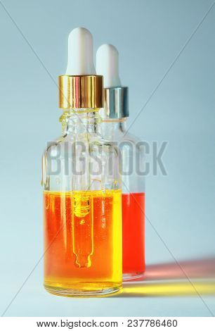 Two Bubbles Of Useful Cosmetic Oil In Transparent Glass Bottles On Bright Background