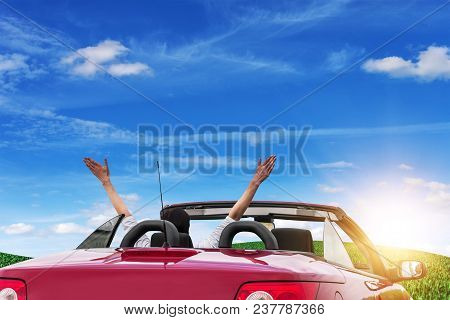 Young Woman In A Car With A Convertible On The Road To The Nature On A Sunny Day. A Woman Raises Her