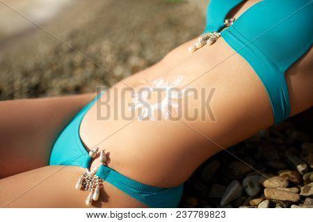 Sunscreen Lotion Drawn On Tanned Woman Belly Skin As Sun Shape. Suntan Cream Applied On Body. Suncre