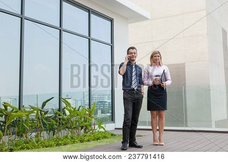 Content Attractive Male And Female Business People Relaxing Outdoors On Modern Office Rooftop With F