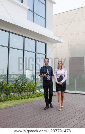 Content Attractive Middle-aged Male And Female Business People Walking Outdoors With Building In Bac