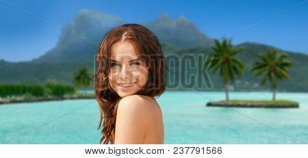 travel, tourism, summer holidays and vacation concept - happy young woman posing in bikini swimsuit at touristic resort over bora bora island beach background