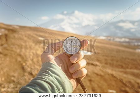 A Man's Hand Holds A Hand-held Compass Against The Backdrop Of Mountains And Hills At Sunset. The Co