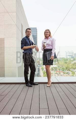Smiling Attractive Business People Relaxing And Drinking On Office Roof With City View In Background