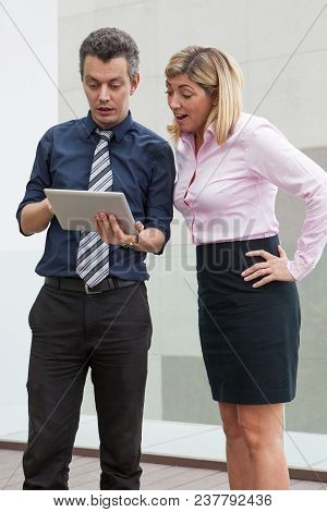 Surprised Male And Female Business People Browsing On Tablet Computer Outdoors. Businesspeople Stand