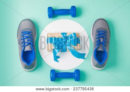Holiday, Birthday, Party Sport Flat Lay Composition With Blue Dumbbells, Gray Shoes, Gift Box On Whi