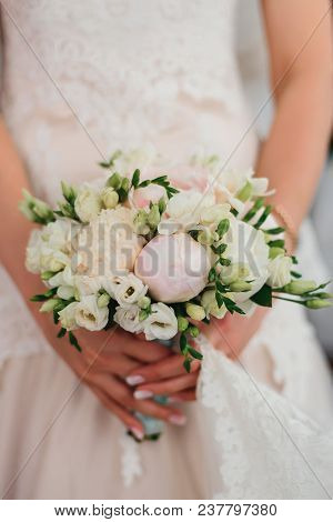 Bride Holds A Delicate Elegant Bridal Bouquet With White Peonies On The Backdrop Of The Dress