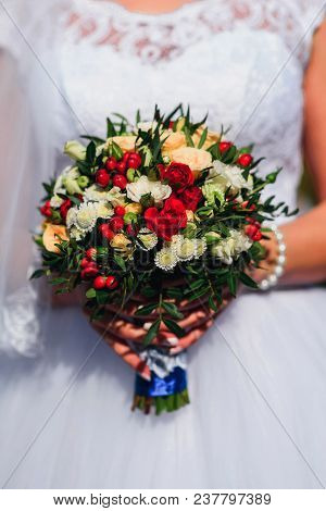 Wedding Bouquet With Red Roses And White Daisies In The Hands Of The Bride On The Background Of The