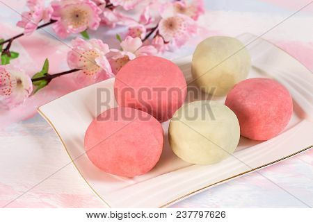 Multicolored Daifuku Mochi Stuffed With Sweet Bean Paste And Strawberry On Plate, Cup Of Tea And Flo