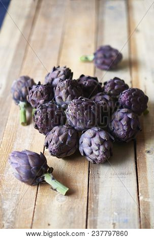 Fresh Purple Artichokes Over A Rustic Wooden Table.