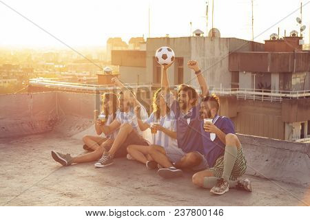 Group Of Young Friends Watching A Football Match On A Building Rooftop, Cheering And Drinking Beer.