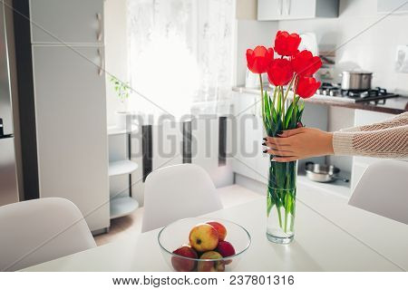 Woman Puts Tulips In Vase. Young Housewife Taking Care Of Coziness In Kitchen. Modern Kitchen Design