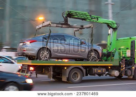 Tow Truck Transports Cars On City Street
