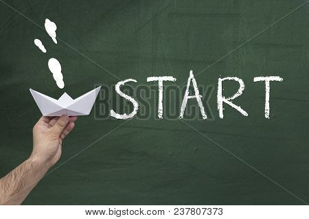 Start, New Business Concept. Human Hand Holding Paper Boat Against Green Blackboard With Text: Start