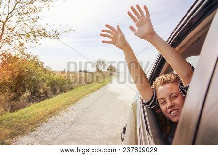 Boy putting his heads and hands out of the car window driving do