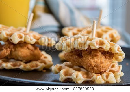 Three Chicken And Waffle Sliders On Cast Iron Skillet Background