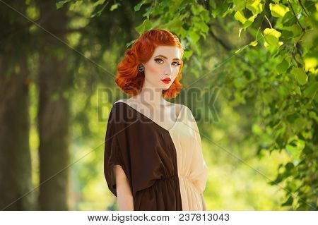 Red-haired Girl In A Free Flying Dress And Retro Hairstyle Against A Spring Park Background. Woman O