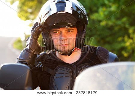 rider on a motorcycle taking off his helmet - summer road trip on a motorbike