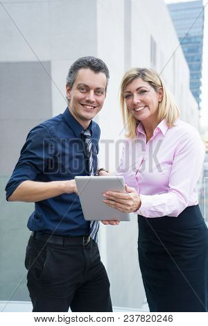 Positive Successful Business Specialists Discussing Plan While Using Tablet Outdoors. Cheerful Confi