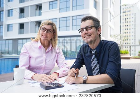 Smiling Ambitious Accountants Contemplating While Sitting At Table With Papers And Calculator Outdoo