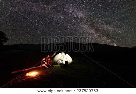 Father And Two Children Tourists Resting At Night Camping In Mountains, Sitting On Log Beside Campfi