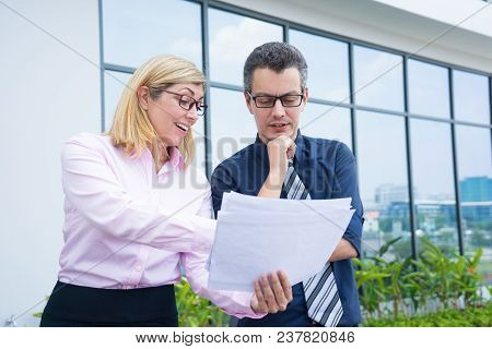 Content Business Partners Discussing Papers Outside Office. Smiling Woman In Formal Shirt Showing So